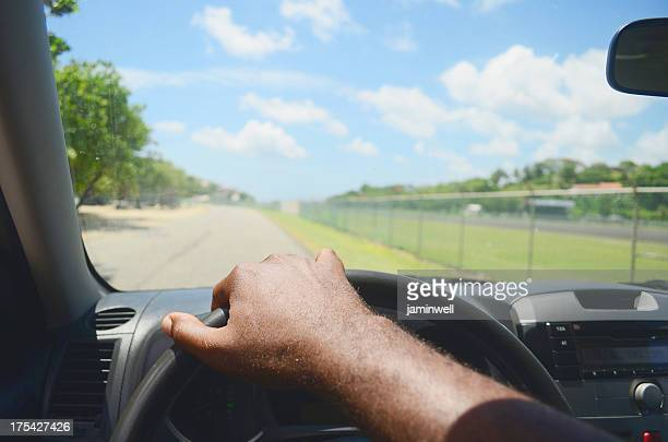 Man's hand on the steering wheel driving down a road