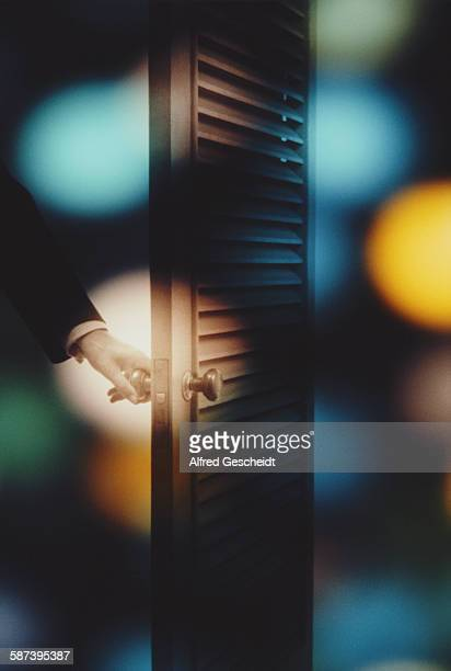 A man's hand opening a slatted door 1982