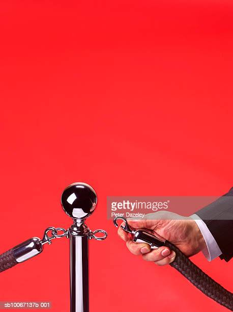 man's hand opening barrier at red carpet event, close-up - doorman stock photos and pictures