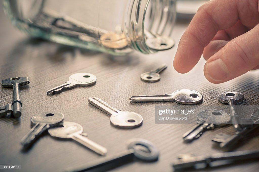 Mans hand picking up keys : Stock Photo