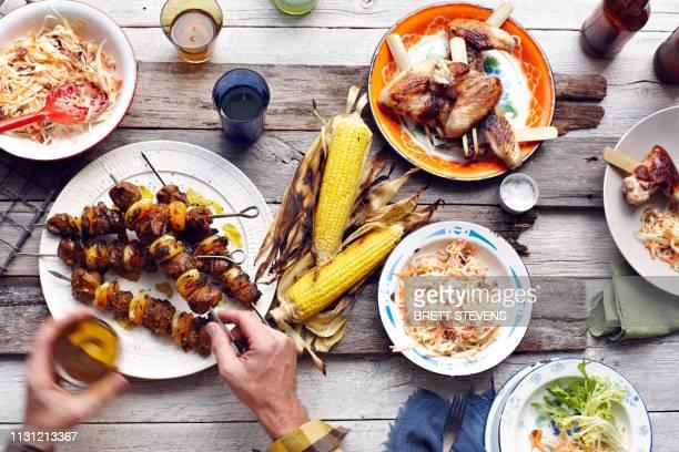 mans hand picking up lamb and chicken skewer from table - grillen stock-fotos und bilder