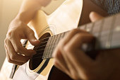 Man's hand playing acoustic guitar