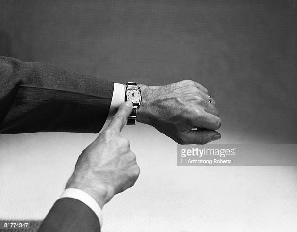 Man's hand pointing at wristwatch. (Photo by H. Armstrong Roberts/Retrofile/Getty Images)