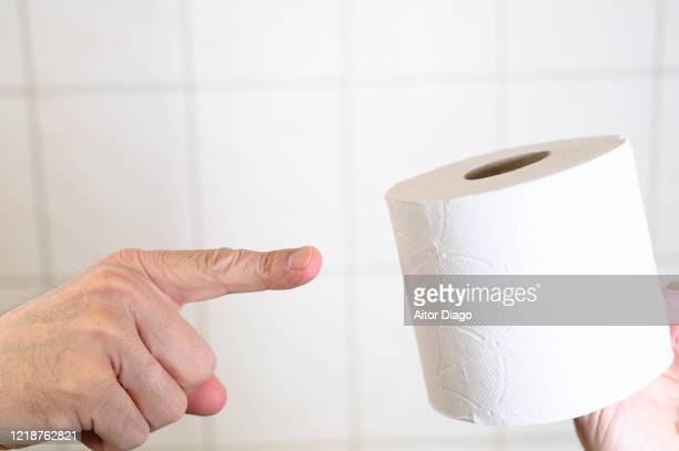 man's hand pointing out with his index finger a toilet paper in bathroom. - hemorroide fotografías e imágenes de stock