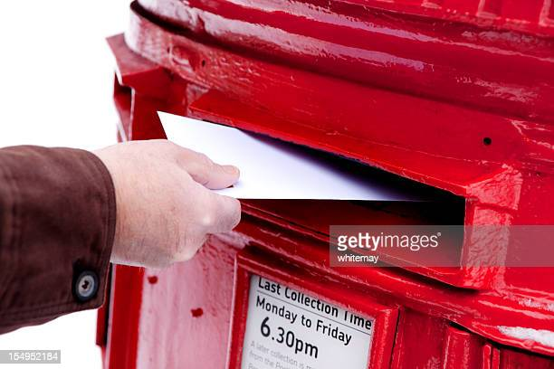 Man's hand posting letter in a snowy British postbox
