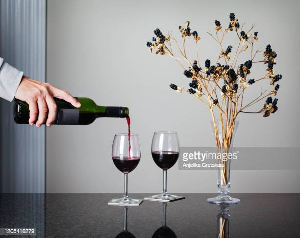 man's hand pouring wine to glass. two glasses of red wine and decorative flowers on the table. - uvas cabernet sauvignon - fotografias e filmes do acervo
