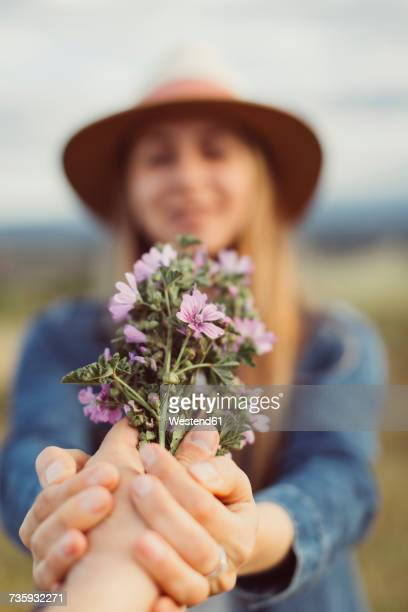 Mans hand presenting woman picked flowers