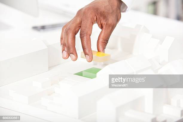 Mans hand putting building block on architectural model, close-up