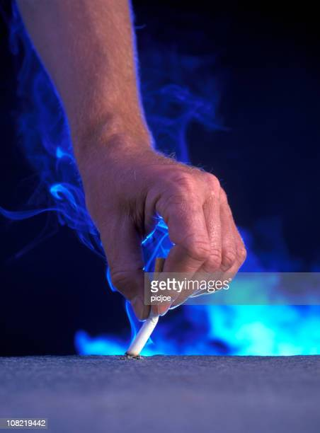 Man's hand putting out cigarette