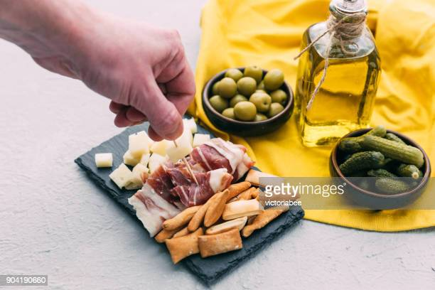 mans hand reaching for spanish tapas - tapas stock photos and pictures