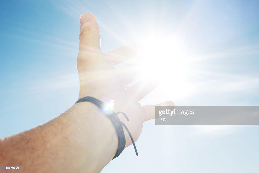 Mans hand reaching for sun : ストックフォト