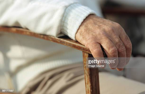 Man's hand resting on chair