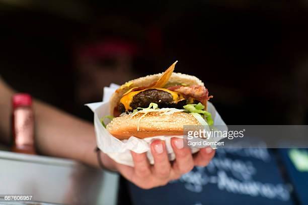 mans hand serving hamburger from fast food van - schnellimbiss stock-fotos und bilder