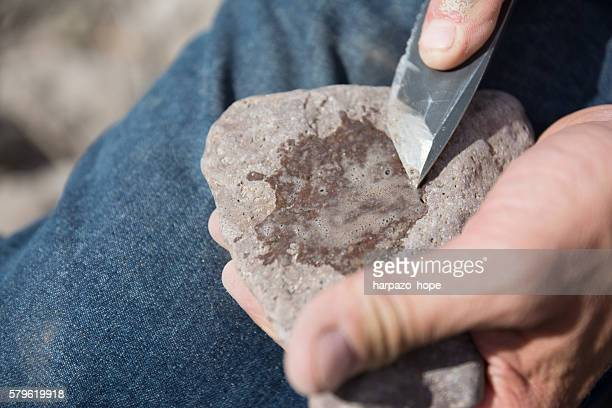 man's hand sharpening a knife. - flint tool stock photos and pictures