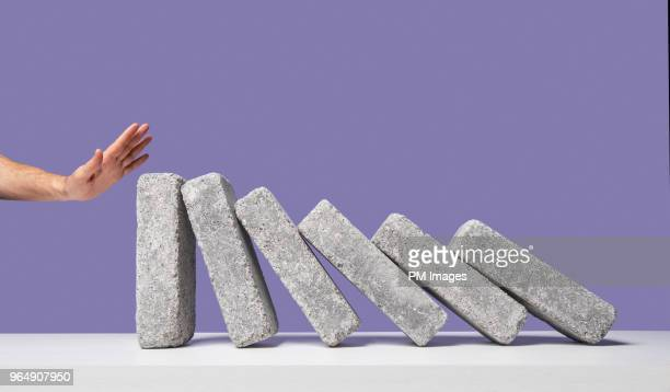 Man's hand stopping domino effect