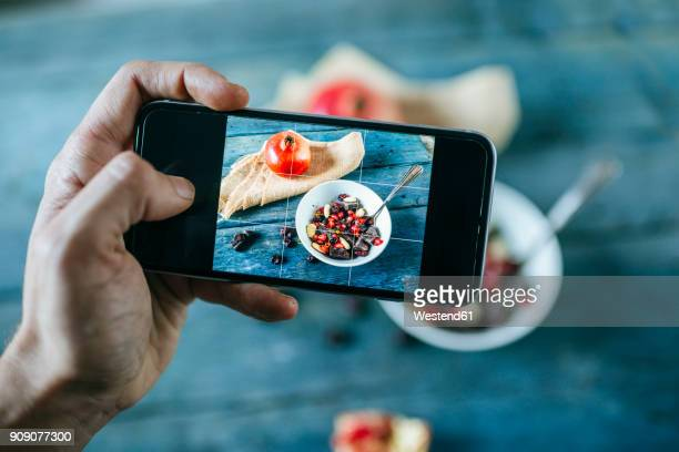 Man's hand taking a picture with smartphone of bowl with dessert of almonds, pomegranate and chocolate