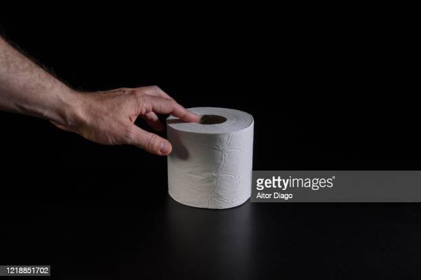man's hand taking a roll of hygienic paper. - hemorroida imagens e fotografias de stock