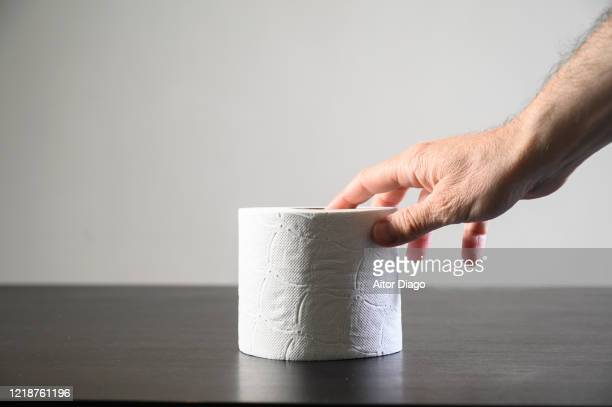 man's hand taking a roll of toilet paper which is on a table indoors. - hemorroide fotografías e imágenes de stock