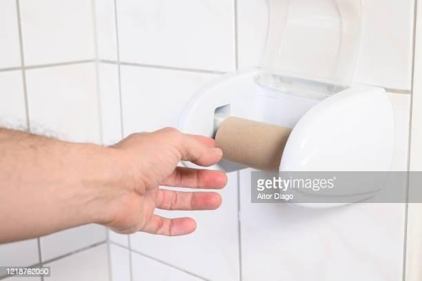 man's hand taking an empty toilet paper in a wc. - hemorroide fotografías e imágenes de stock
