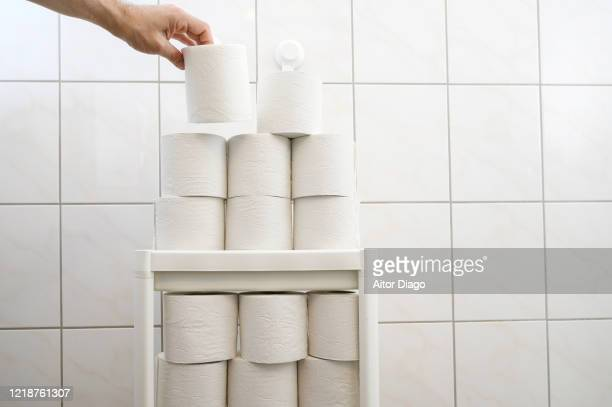 man's hand taking one of the many roll of toilet paper that are stored in the toilet. - hemorroida imagens e fotografias de stock