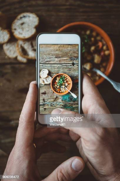 Mans hand taking picture of Mediterranean soup in bowl, close-up