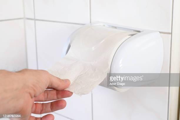 man's hand taking toilet paper in a wc. - hemorroide fotografías e imágenes de stock