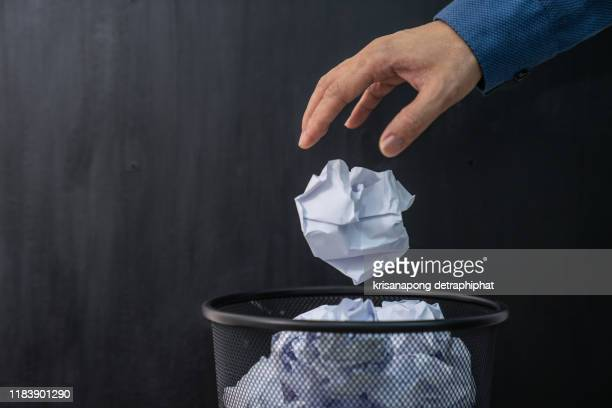 man's hand throwing crumpled paper in basket - the_writer's_block stock pictures, royalty-free photos & images