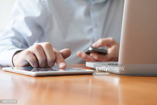 Mans hand typing on touch screen of digital tablet