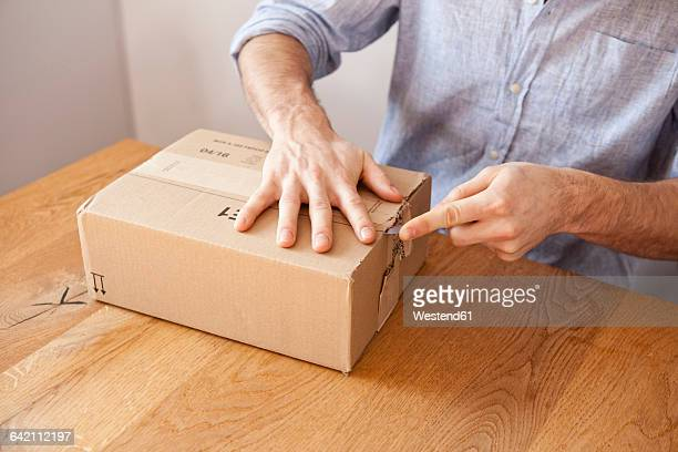 Mans hand unpacking cardboard box with a knife