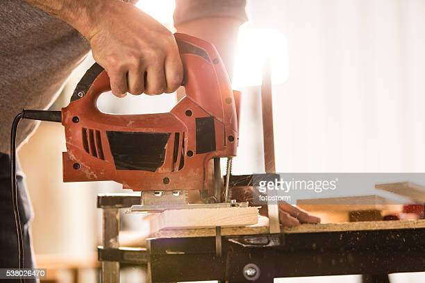 Man's hand using electric jigsaw