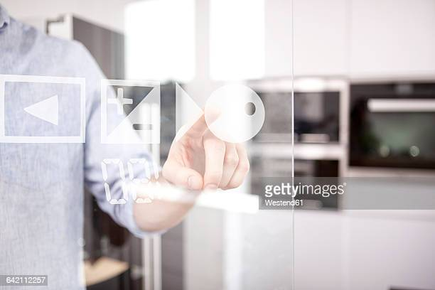 Mans hand using touchscreen of oven in his kitchen