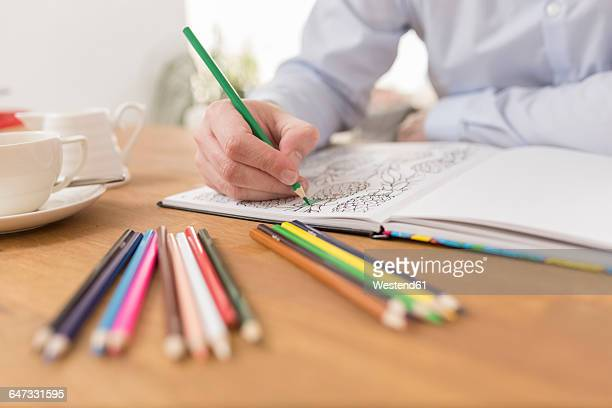 man's hand with colouring book and coloured pencils, close-up - colouring book stock photos and pictures