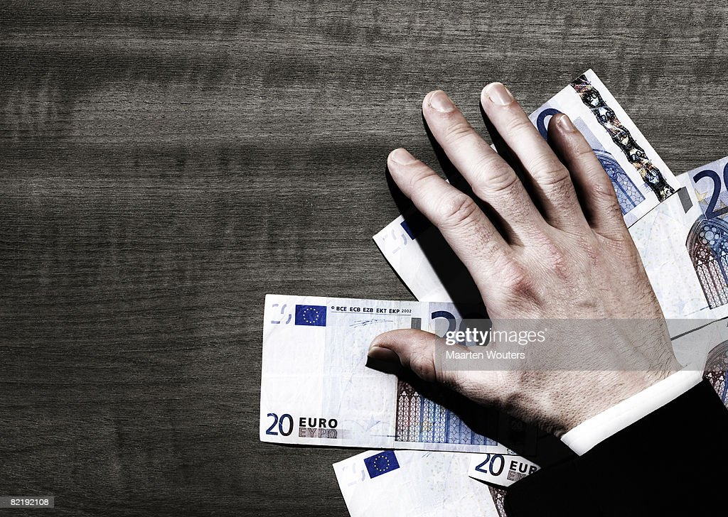 Man's hand with euro notes on ta : Stock Photo