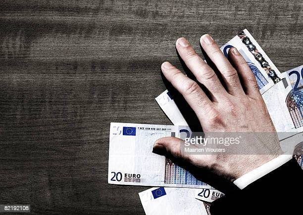 Man's hand with euro notes on ta