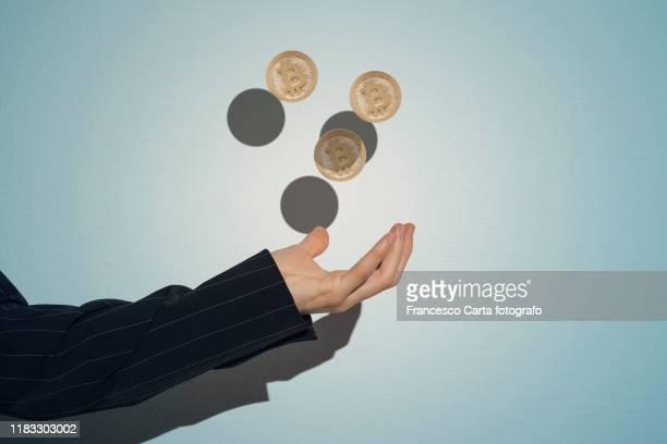 man's hand with gold bitcoins - kryptowährung stock-fotos und bilder