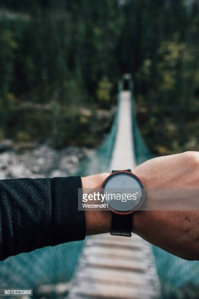 man's hand with watch in front of swinging bridge - wrist stock pictures, royalty-free photos & images