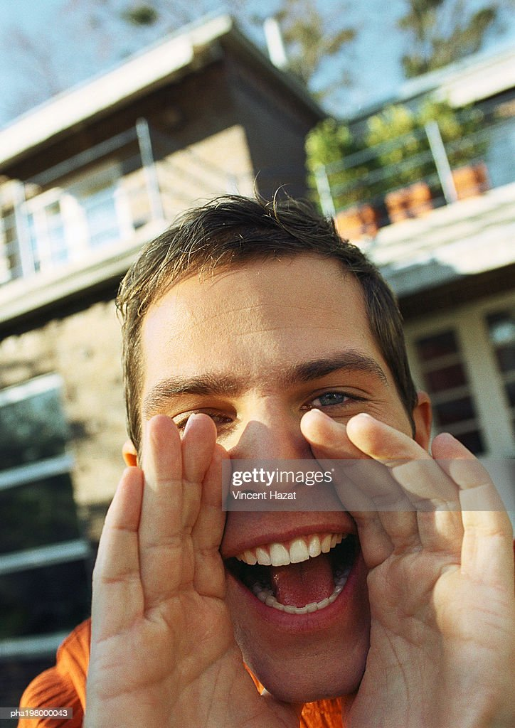 Man's hands around open mouth, close-up, house in background : Stockfoto