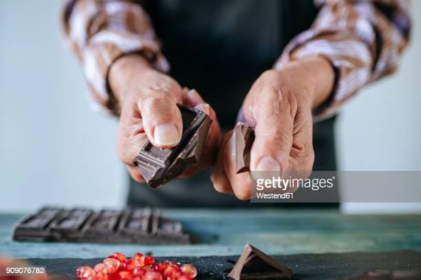 man's hands breaking a chocolate bar, close-up - chocolate making stock pictures, royalty-free photos & images