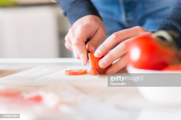 Man's hands chopping tomato