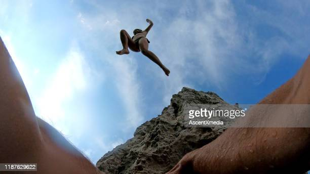 pov of man's hands climbing up seaside cliff - simple living stock pictures, royalty-free photos & images