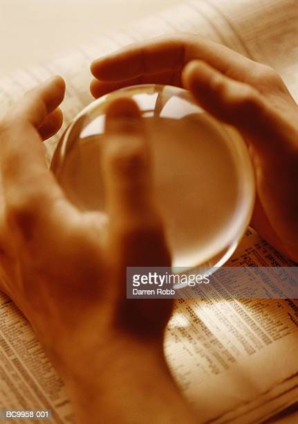 man's hands cupped around crystal ball on financial newspaper - 囲む ストックフォトと画像