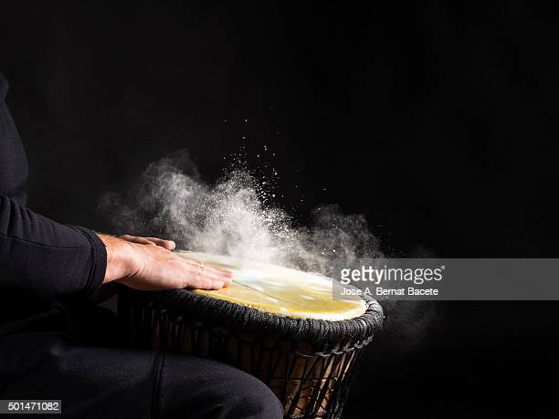 Man's Hands Drumming on Bongo Drum, with a cloud of powder to around