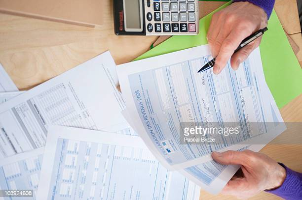 Man's hands filling his tax form