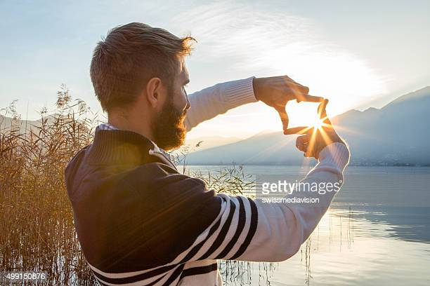 Man's hands frame sunset over mountain lake