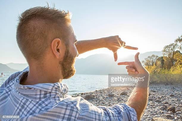 Mann Hand-frame Sonnenuntergang über mountain lake