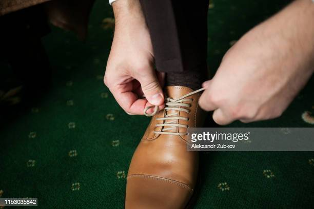man's hands, groom, businessman tying the laces of his new brown leather business shoes, green carpet background, close-up. the concept of business, entrepreneurship, fashion. - beige shoe stock pictures, royalty-free photos & images