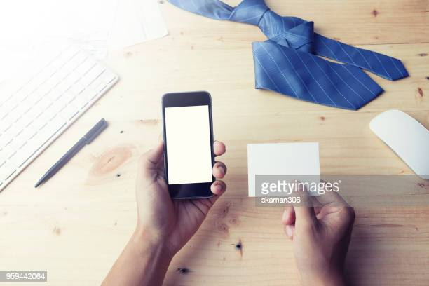 Man's hands holding a blank card and using smart phone for business