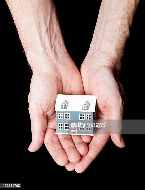 man's hands holding a house