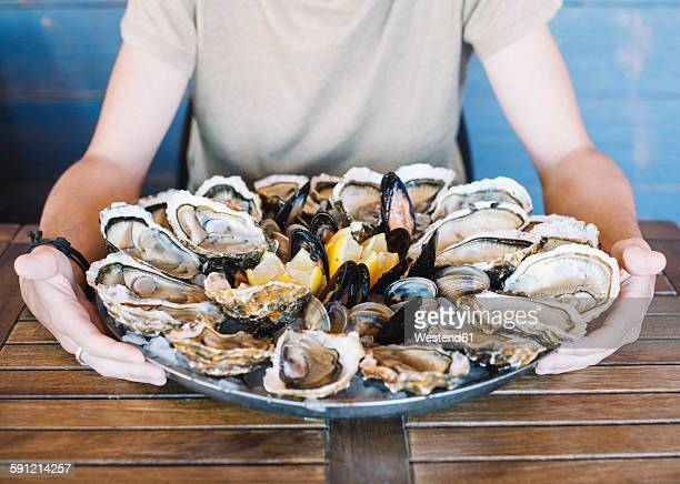Mans hands holding a seafood platter with oysters, clams and mussels.