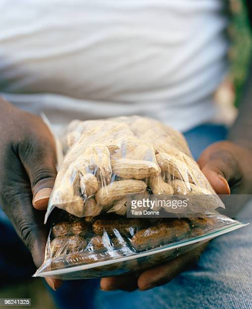 man's hands holding bags of peanuts - boiled stock pictures, royalty-free photos & images